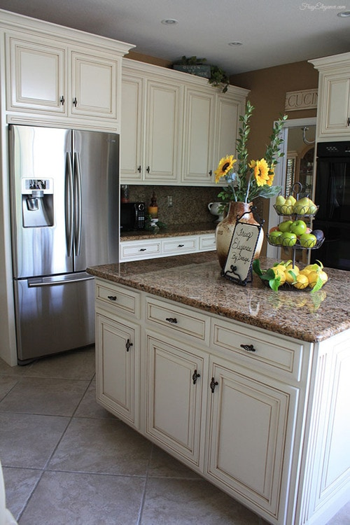 A kitchen island with cream cabinets and brown granite counters