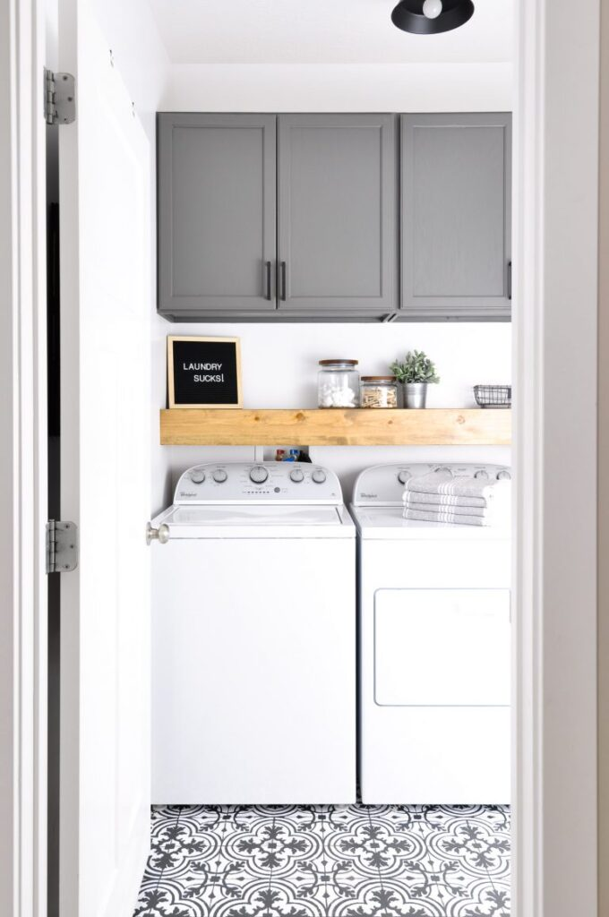A laundry room with grey cabinets and a decorative floor