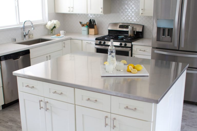 A kitchen island with stainless steel countertops