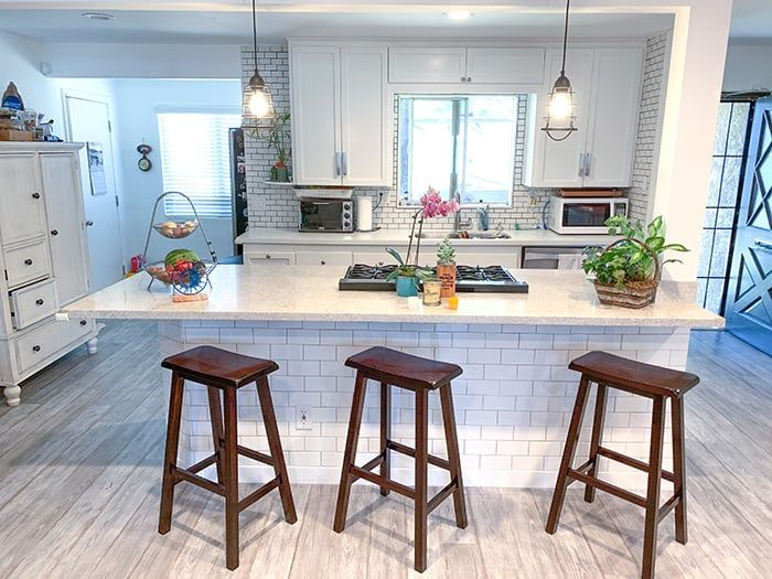 A white granite kitchen island with white subway tiles