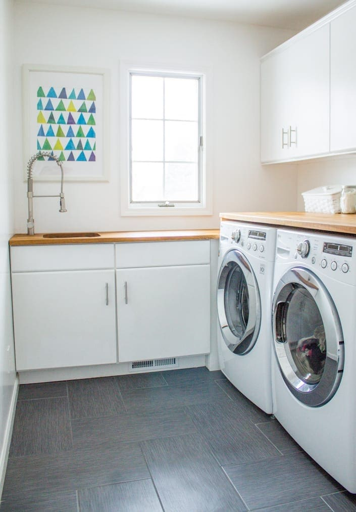 A piece of art hangs above the sink in a laundry room