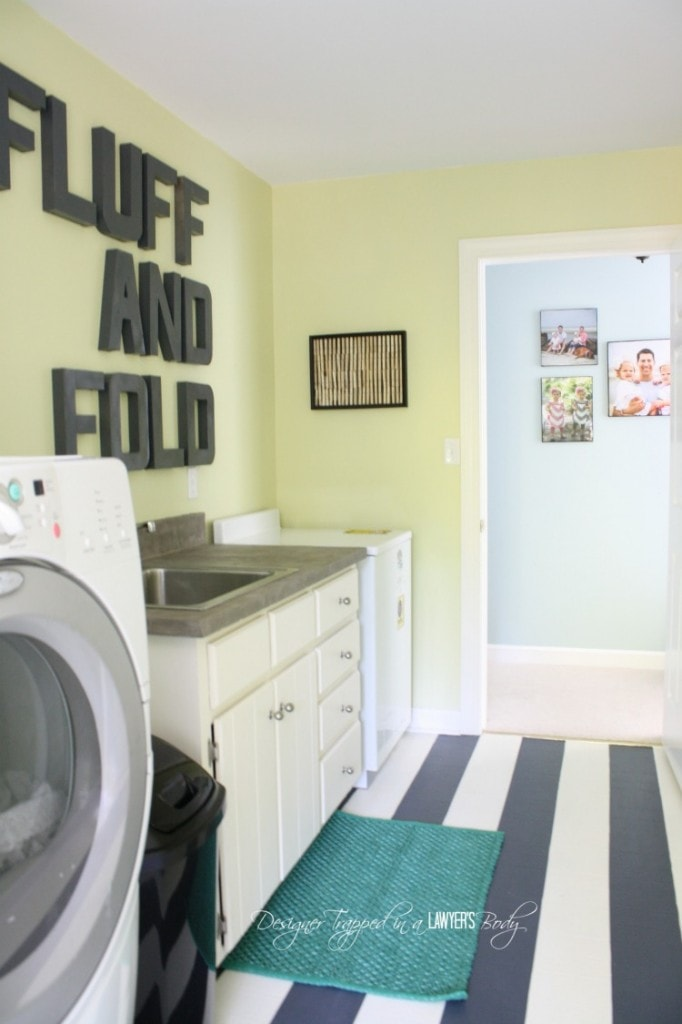 A laundry room with striped floors and the words fluff and fold on the wall