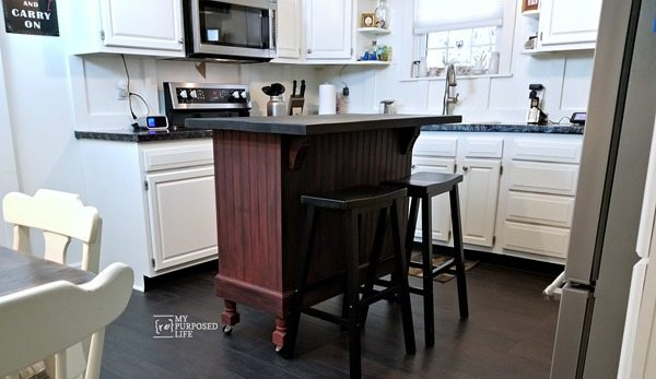 A kitchen island with wheels and 2 stools