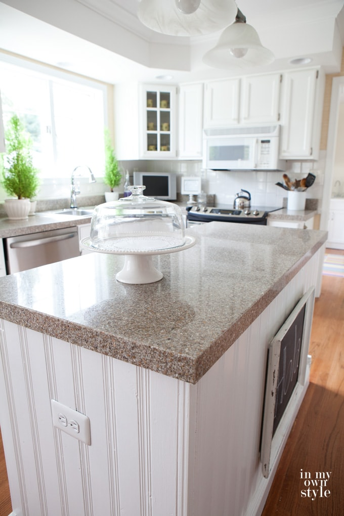 a white kitchen island with granite countertops