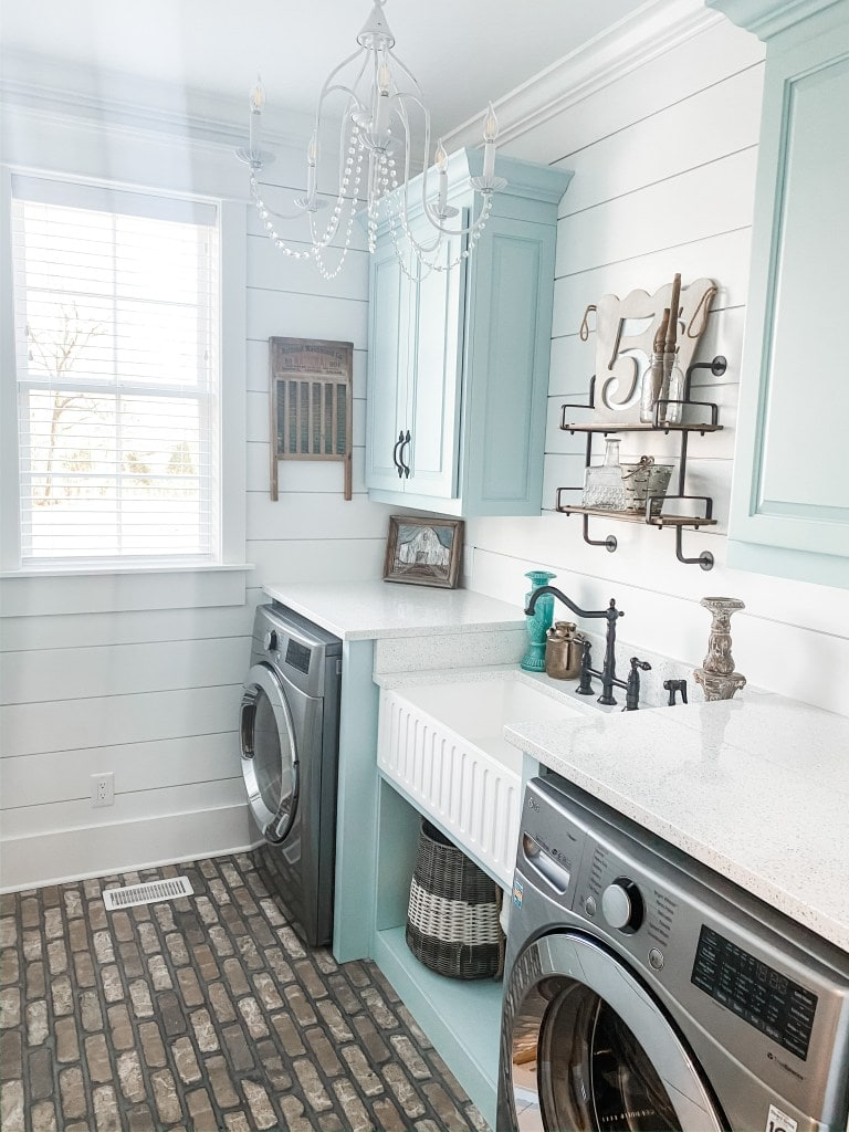 A laundry room with brick floor and a chandelier