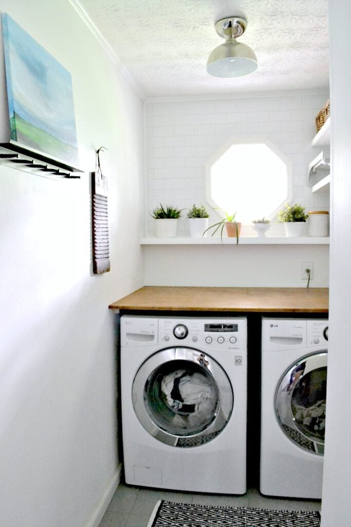 A laundry room with white bricks on the wall