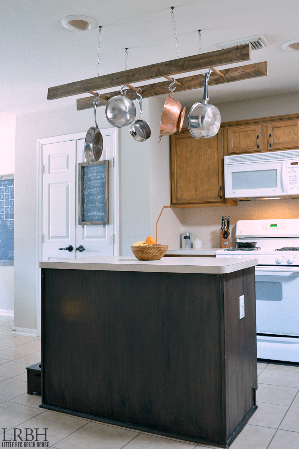 Pots and pans hanging from the ceiling above the kitchen island