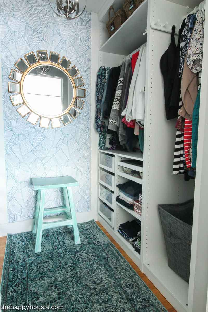 An organized closet with a blue wall and mirror