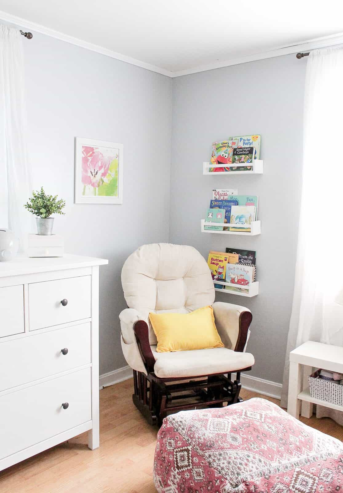 A rocking chair and books on the wall in a nursery