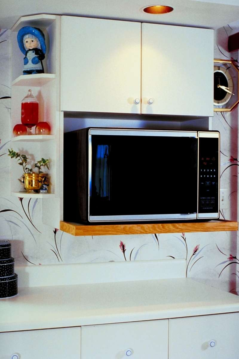 A great option for those wondering where to put microwave in small kitchen is to use shelving place the microwave under high cabinets.