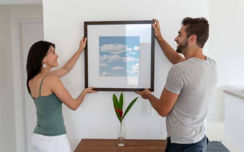 Two people holding a framed piece of art in an article about alternatives to command strips for hanging decor